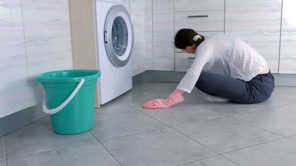Woman in pink rubber gloves washes kitchen furniture with cloth. sitting on the floor. Side view.