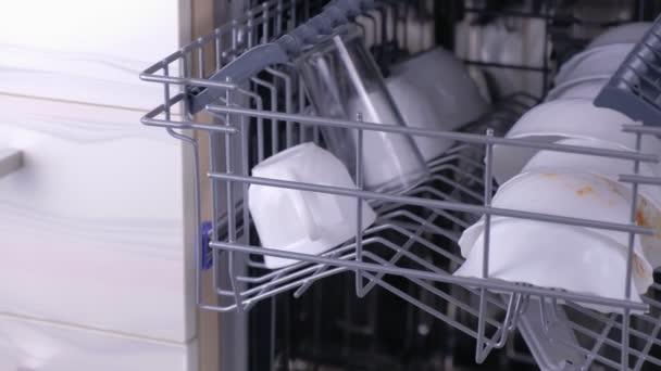Špinavá bílá jídla v koši na nádobí v kuchyni.