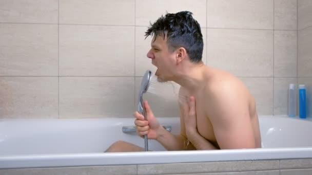 Člověk zpívá, zatímco se pere ve vaně.