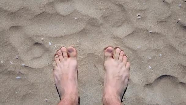 Na písečné pláži za slunečného dne stojí Mans..