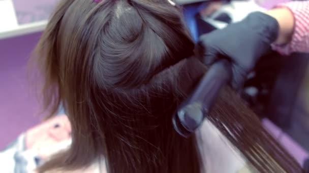 Kadeřník rovinky tmavě hnědé vlasy krásné ženy pomocí kleští vlasů v salonu krásy.