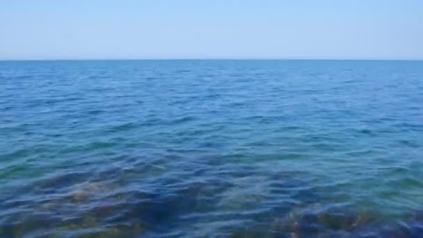 Modrá a čistá hladina mořské vody s oblohou, pohled z boku.