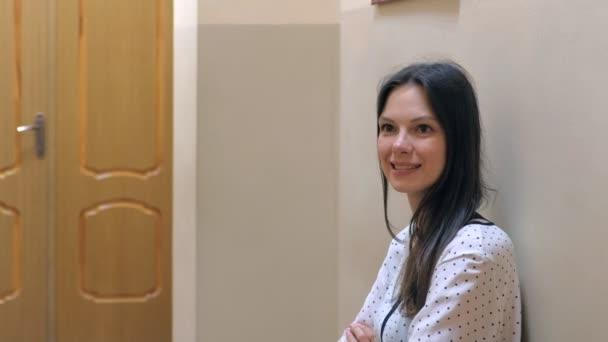 Lächelnde Sorgenfrau wartet vor der Tür auf Vorstellungsgespräch.