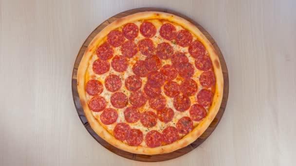 Pizza salám na dřevěné desce na stole. Pohled shora detail.