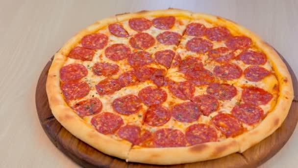 Krájení salámu pizzu na dřevěné desce na stole. Detail boční pohled.