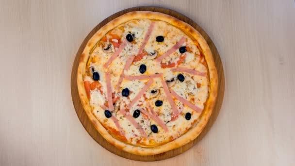 Pizza se šunkou a sýrem na dřevěné desce na stole. Zobrazení zblízka.
