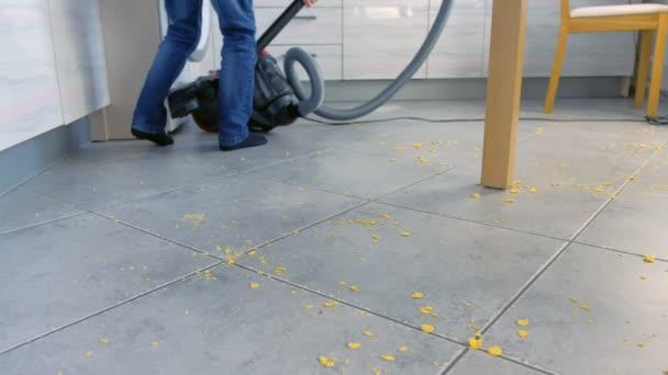 kleiner Junge beim Absaugen des Küchenbodens. Er räumt die auf der grauen Fliese verstreuten Cornflakes auf. Beine aus nächster Nähe.
