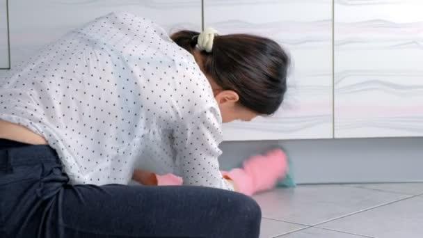 Žena v růžových gumičkách omyje pevný kuchyňský nábytek látkou. sedí na podlaze. Pohled zezadu.