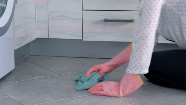 Žena v růžových gumičkách omyje pevný kuchyňský nábytek látkou. sedí na podlaze. Pohled ze strany.