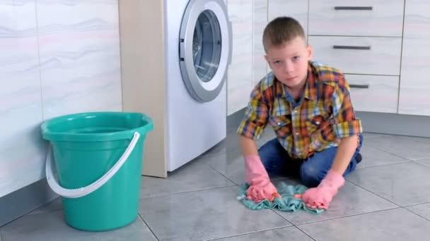 Müder Junge in Gummihandschuhen wäscht den Boden in der Küche und schaut in die Kamera. Kinderheim-Pflichten.
