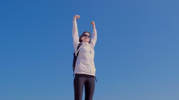 glückliche Gewinnerin in Siegerpose mit erhobenen Händen auf blauem Himmelhintergrund.