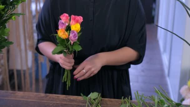 Nő virágüzlet tesz egy csokor színes rózsák virágbolt, kezek Vértes.