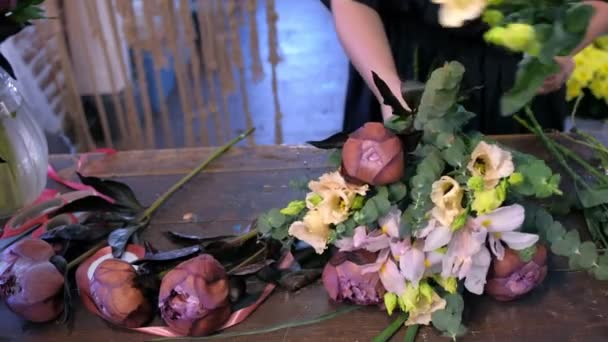 Florist creates bouquet of eucalyptus, eustoma, peony and iris in flower shop.