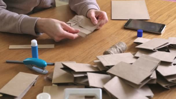 Žena vyrábí papírové tašky z kraftu papíru pro Adventní kalendář. Uzavření rukou.