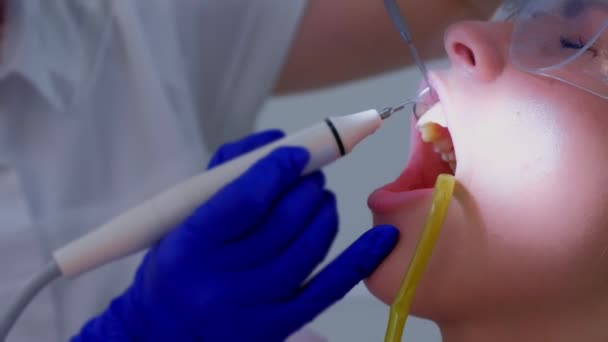 Dental hygienist dentist makes ultrasonic cleaning teeth to woman, closeup view.