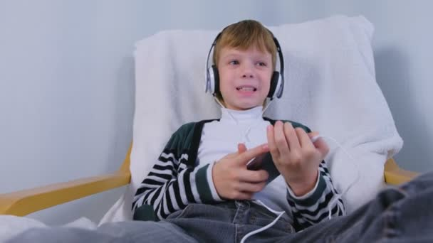 Boy is listening music in headphones in smartphone and singing sitting in armchair at home.