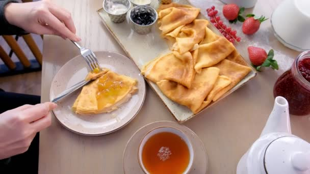 Žena je jíst ruské tradiční palačinky, Bliny servírovaná s džemy, zakysanou smetanou a jahody na desce. A pití čaje. Detail boční pohled.