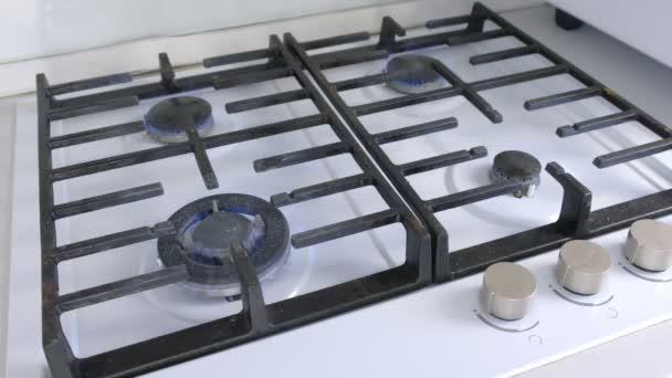 Čtyři hořící plynové hořáky z kuchyňského plynového sporáku. Plynový sporák s mřížkou.