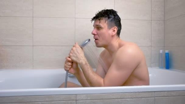 Člověk zpívá, zatímco se pere ve vaně. Ve sprše nalévá vodu na hlavu.
