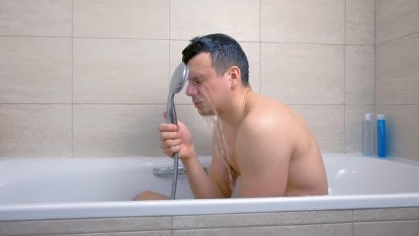 Unavený muž se pere ve vaně. Nalévání vody na obličeji ze sprchy.