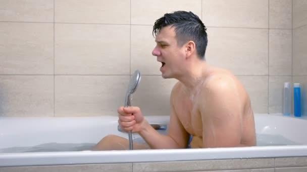 Člověk zpívá s nadšením, zatímco se pere ve vaně.