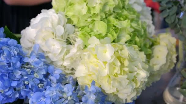 Florist woman makes bunch of hydrangea flowers in shop to sale, flowers closeup.