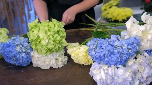 Florist woman making bouquet of hydrangea flowers in shop, hands closeup.