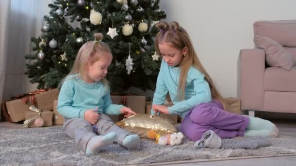 Two girls sisters draw fingers on pillow with sequins sit near Christmas tree.