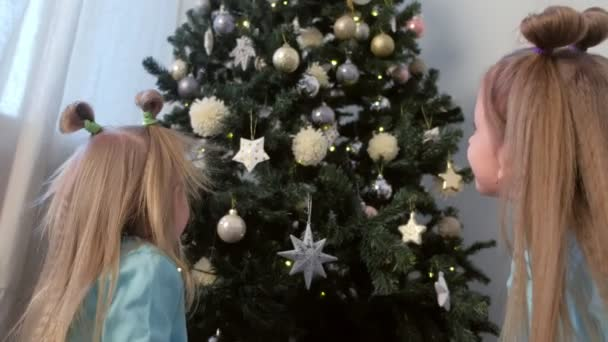 Two girls sisters decortaing Christmas Tree with toys snowflakes and stars.