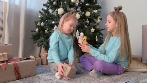 Two girls sisters playing with snowman toys sitting near Christmas tree at home.