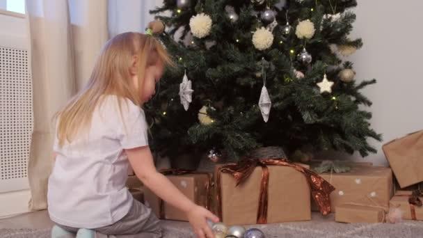 kleines Mädchen entfernt Spielzeug Sterne Kugeln von Weihnachtsbaum spielt zählt es.