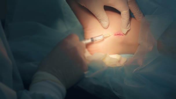 Chirurg vstřikující lék pro lokální anestezii během operace k zašití rány.