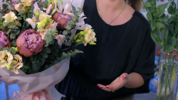 Woman florist shows big frower bouquet in white paper in shop, hands closeup.