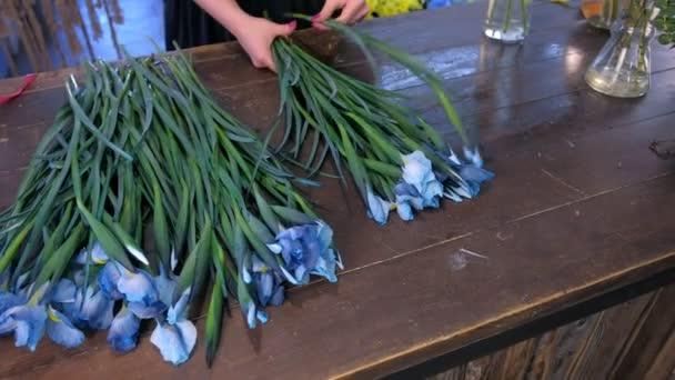 Květinářství žena vytváří kytice z modré duhovky květiny na stole na prodej v obchodě.