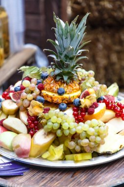 Sliced fruits and berries (pineapple, grapes,apples, bananas, raspberries, blueberries, and others) lie on a plate slide.