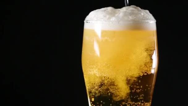 Světlé pivo se nalije do rotující sklo na černém pozadí.