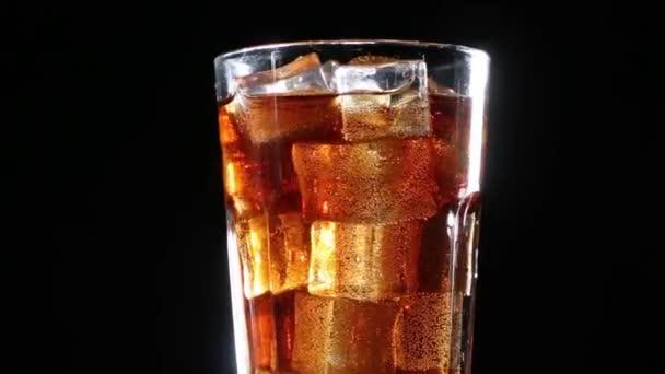 Cola mit Blasen in ein Glas Eis.Schwarzer Hintergrund gegossen