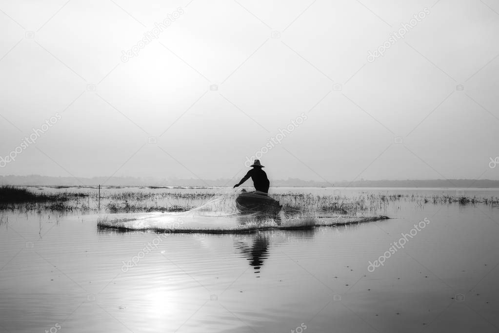 Black and white of fishermen casting for catching the fish on the wooden boat at the lake in the morning. Thailand lifestyle.