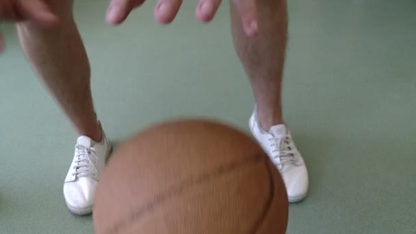 A young man is getting stronger with a basketball. Slowmotion shot