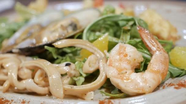 filmt die Kamera einen appetitlichen Fischsalat. gesundes Ernährungskonzept.