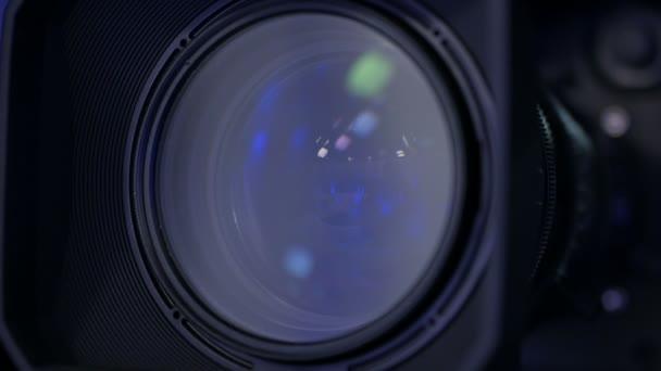 Közelről egy professzionális kamera lencséje egy stúdióban sötét háttéren