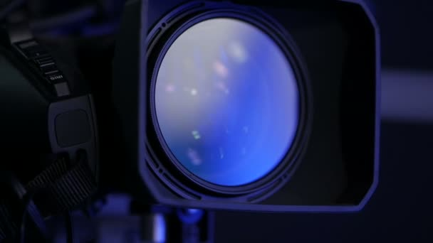 Close-up of a professional camera lens in a studio on a dark background