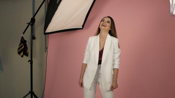 Usmívající se krásná brunetka mladá žena izolované na růžovém pozadí studia.