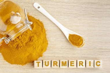 turmeric powder in glass bowl on wood- curcuma longa