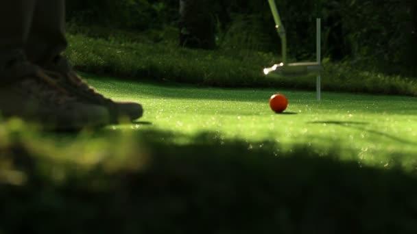 Perfect golf putt. Three orange balls
