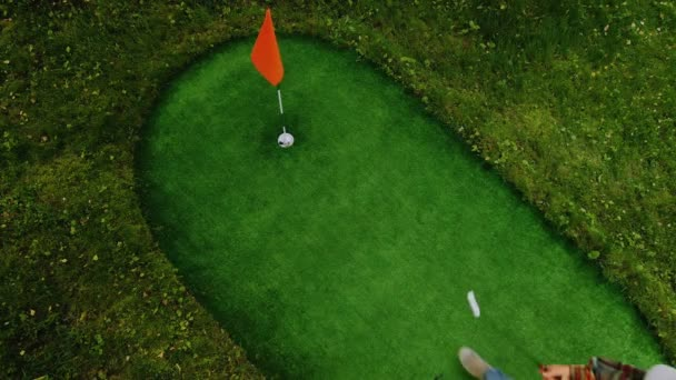 Golf sport concept, slow motion golfer putting golf ball into hole