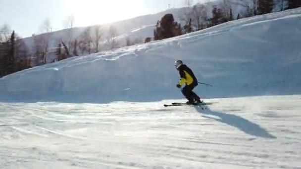Mladý dospělý rekreační lyžař má v chladné zimě idylické dokonalé počasí. Lyžování na perfektně upravené sjezdovce v lyžařském středisku
