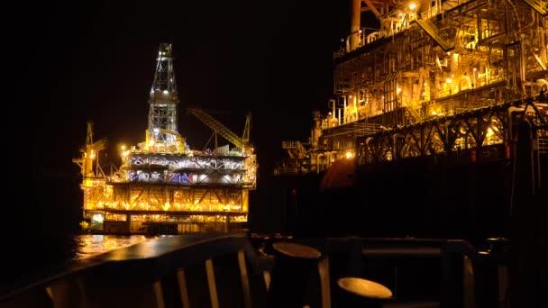 FPSO nave cisterna vicino alla piattaforma petrolifera Rig di notte. Industria di petrolio e gas offshore