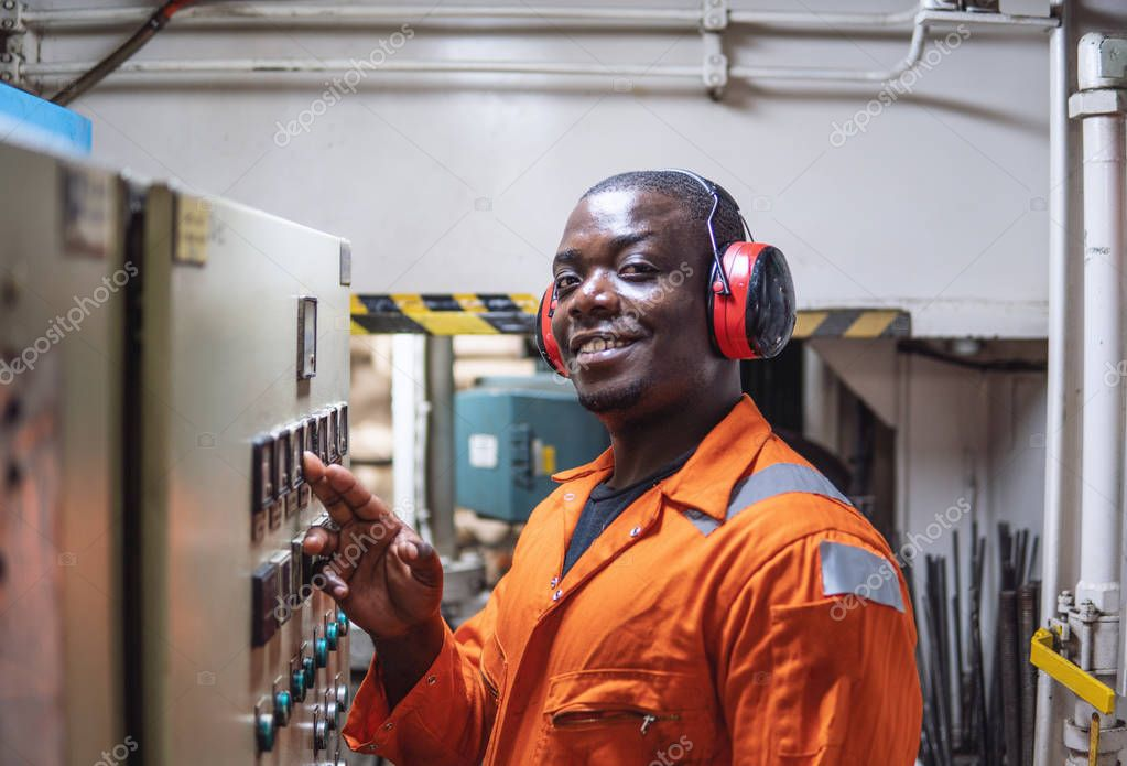 Marine engineer officer in engine control room ECR. Seamens work. He starts or stops main engine of ship