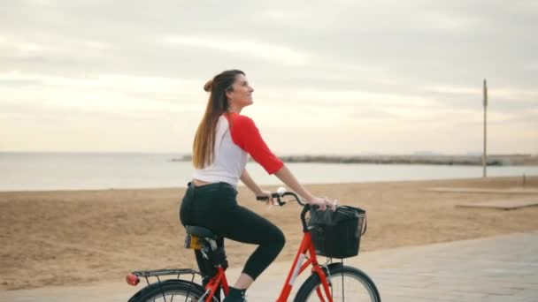 Woman riding bicycle along beach sand at summer time